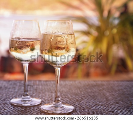 two glasses of white wine with ice on a table at the beach cafe. Image with retro toning - stock photo