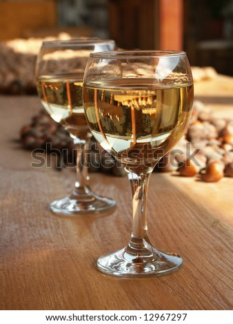 Two glasses of white wine with nuts at the background - stock photo