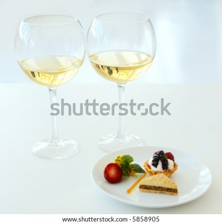 two glasses of white wine with sweets shallow dof - stock photo