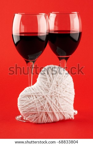 Two glasses of wine and a white heart made of wool on a red background. Valentine's Day