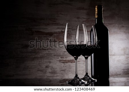 two glasses of wine and bottle over grunge background - stock photo