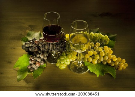 two glasses of wine and different clusters of grapes - stock photo
