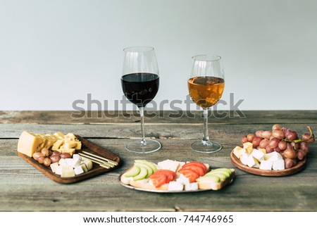 Two glasses of wine and food on a wooden table