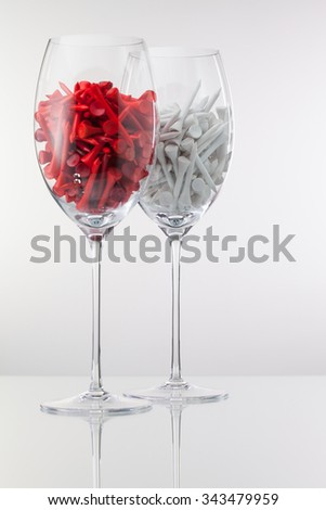 Two glasses of wine and golf equipments on the white background - stock photo