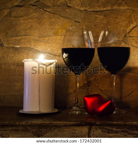 Two glasses of wine, candle and teddy red heart on stone wall background.
