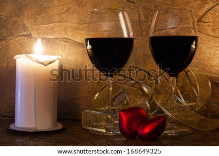 Two glasses of wine, candle and teddy red heart on stone wall background. Valentines day. - stock photo