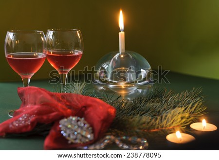 Two glasses of wine, candle, beads, brooch and a branch of a Christmas tree on a green background - stock photo