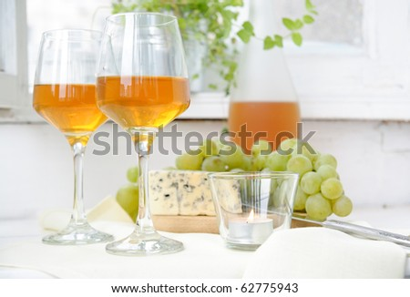 Two glasses of wine, grapes and blue cheese on a light background - stock photo