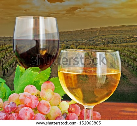 two glasses of wine on a wooden table by a vineyard at dusk - stock photo