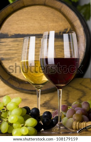 Two glasses of wine, red and white wine with grapes - stock photo