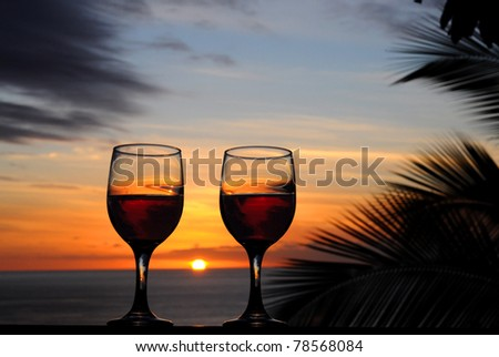 Two glasses of wine reflecting the tropical sunset. - stock photo