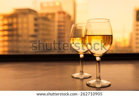 Two glasses of wine with a city background  - stock photo