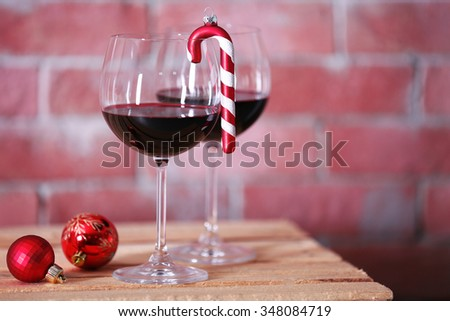 Two glasses of wine with christmas toys on wall background - stock photo