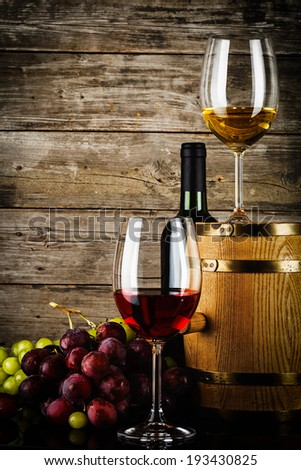 two glasses of wine with fresh grapes, bottle and barrel in front of old grunge wooden planks
