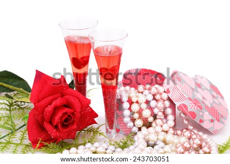 Two glasses, red rose, colorful pearls necklaces and gift box on white background. - stock photo