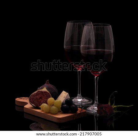 Two glasses red wine with cheese, rose, figs and grapes isolated on black - stock photo