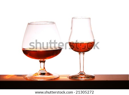 Two glasses with brandy on a white background