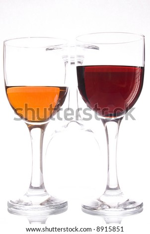 Two glasses with bright liquid and one upturned glass