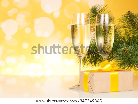 Two glasses with champagne and a gift on a background of trees