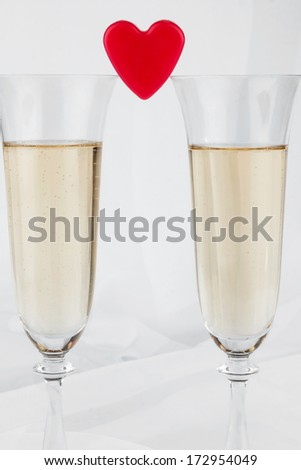 Two glasses with champagne and symbolic heart ,on a white background  - stock photo