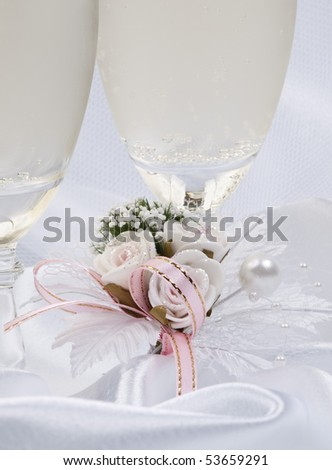 Two glasses with champagne and wedding decoration on white silk - stock photo