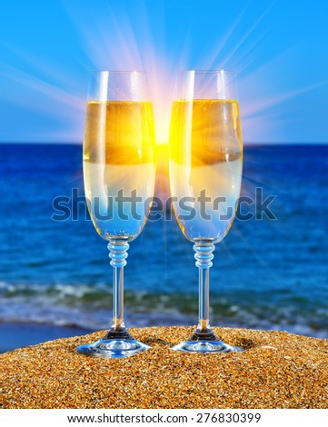 Two glasses with champagne on the beach against the sunset - stock photo