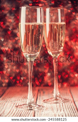 Two glasses with champagne over abstract defocused lights shaped like hearts  - stock photo