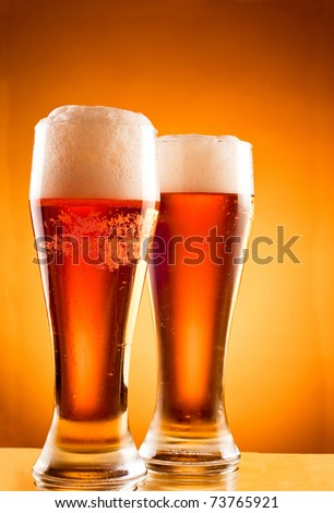 Two glasses with cold beer over yellow background - stock photo