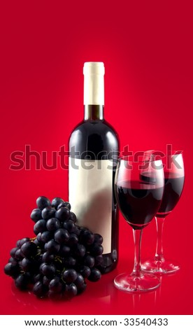 Two glasses with dark red wine on a red background. A dark wine bottle with a white label. Red ripe grape.