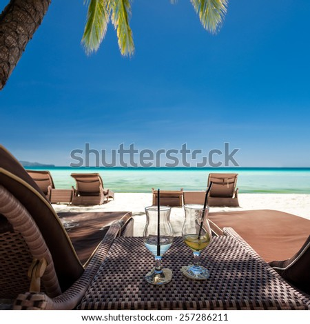 Two glasses with finished up cocktails with straw on tropical beach - stock photo