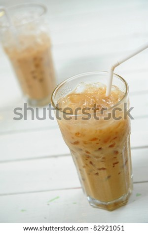 Two glasses with milk, coffee and icecubes - stock photo