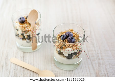 Two glasses with natural yogurt with fresh blueberries and home made muesli cereals, selective focus - stock photo