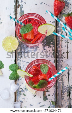 Two glasses with retro cocktail tubes and glass jug of homemade strawberry lemonade, served with fresh strawberries, mint, lime and ice cubes over old white wooden table. See series - stock photo
