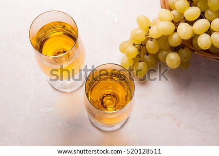 Two glasses with white wine on light marble background. Bunch of green grapes in yellow wooden basket near the glasses.