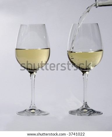 Two glasses with white wine while one glass is filled by a bottle - stock photo