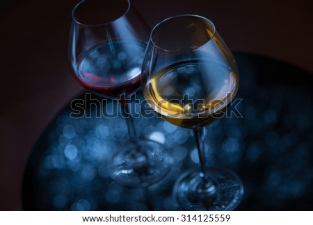 Two glasses with wine, silver defocused lights reflection on dark background - stock photo