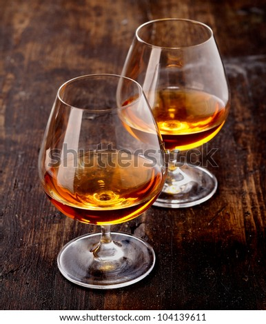 Two goblets of brandy warmed by the glow of the lights on wooden counter top while entertaining a special friend - stock photo