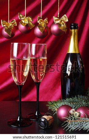 Two goblets of champagne, bottle and new year decoration against purple drapery - stock photo