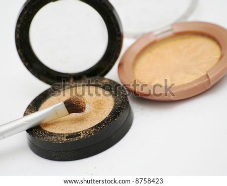 Two gold eyeshadows and brush applicator - stock photo