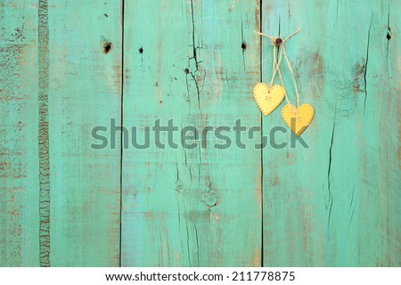 Two gold hearts hanging from rope on antique green weathered wood background - stock photo