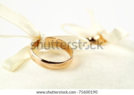 Two gold rings on little pillow. One ring in focus