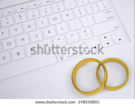 Two gold rings on the keyboard. View from above - stock photo