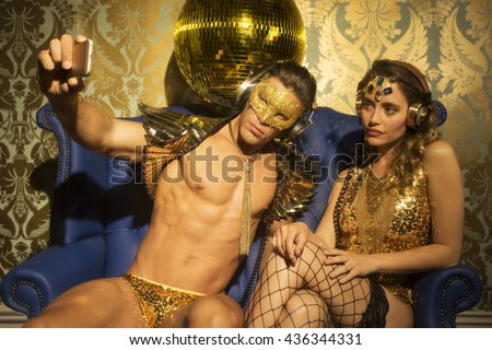 Two gold sexy disco caracters taking a selfie with a mobile phone