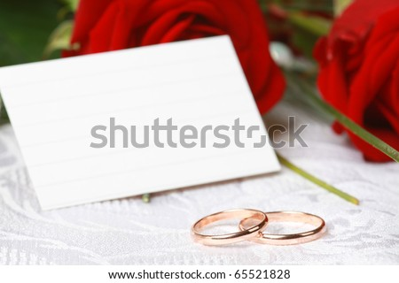 Two gold wedding rings against red rose with card