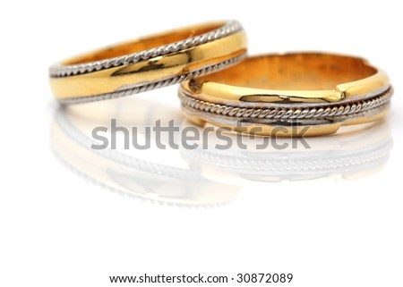 two gold wedding rings closeup reflected with copyspace on white
