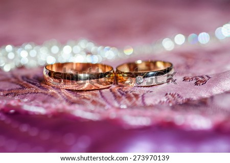 Two gold wedding rings lie on a pillow close up - stock photo