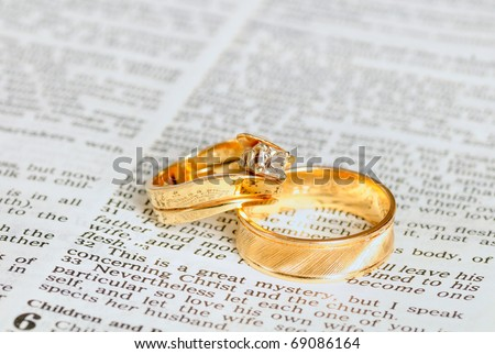 Two gold wedding rings on top of the marriage passage from Ephesians 5 in the Bible - stock photo