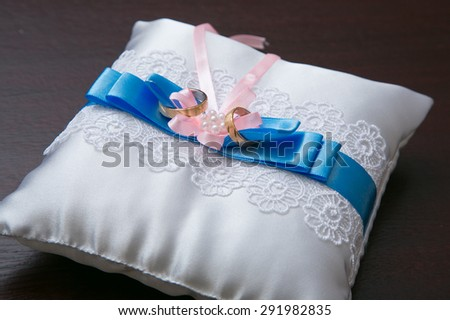 Two gold wedding rings on white and blue lacy pillow - stock photo