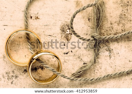 Two gold wedding rings tied with string - stock photo