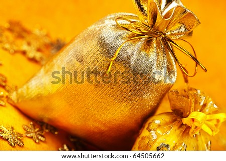 Two golden christmas gift sacks with ribbons over yellow background - stock photo